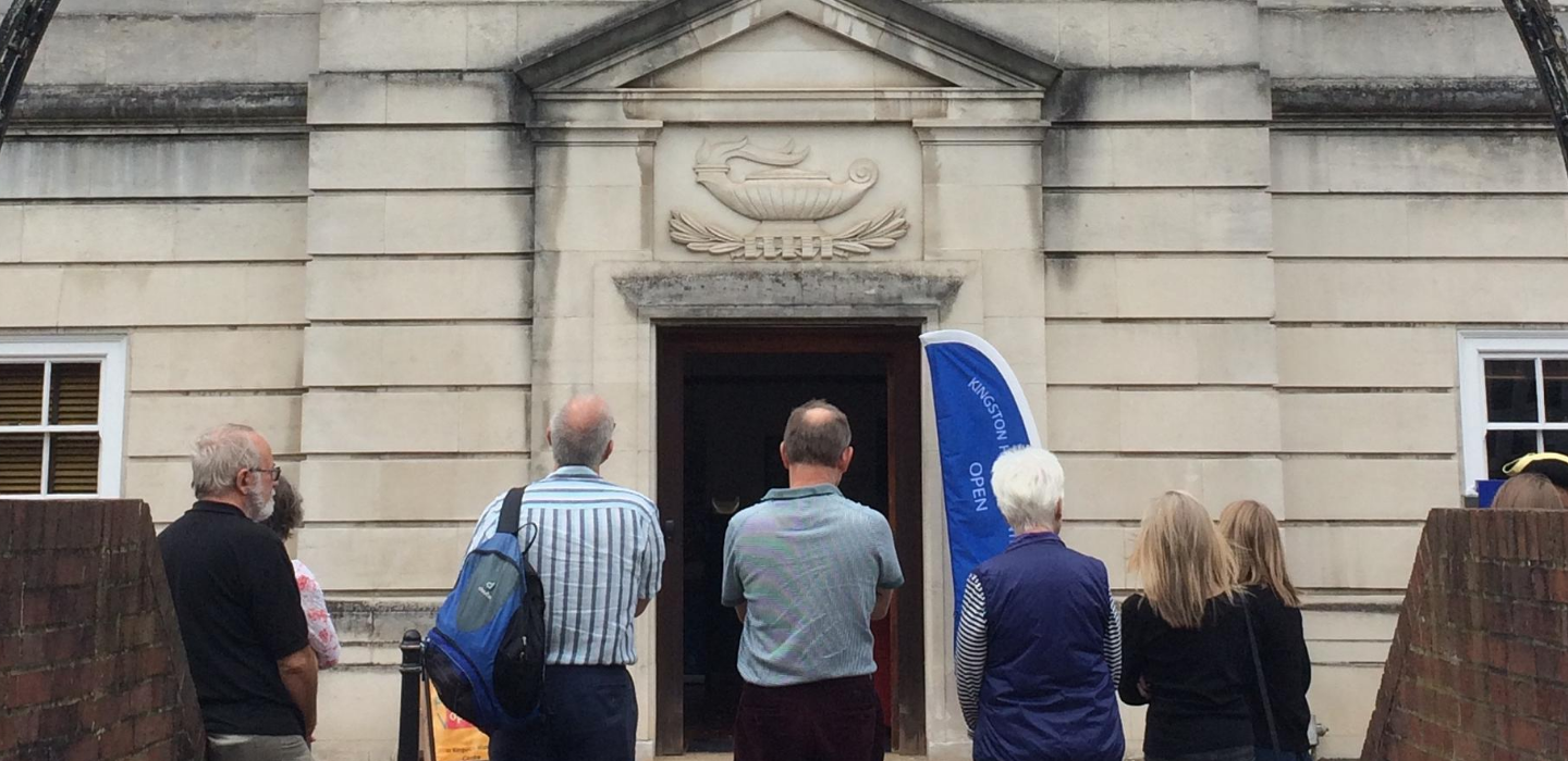 People stood outside Kingston History Centre looking at the door.