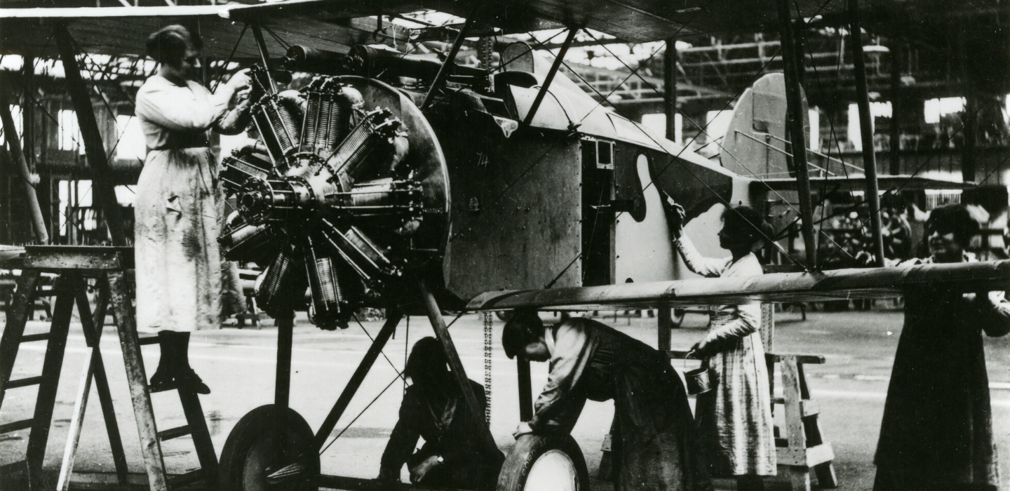 A photograph of women working on a plane in an aircraft factory.