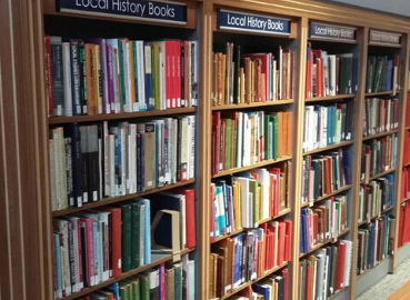 Books on shelves in the local history library at Kingston History Centre