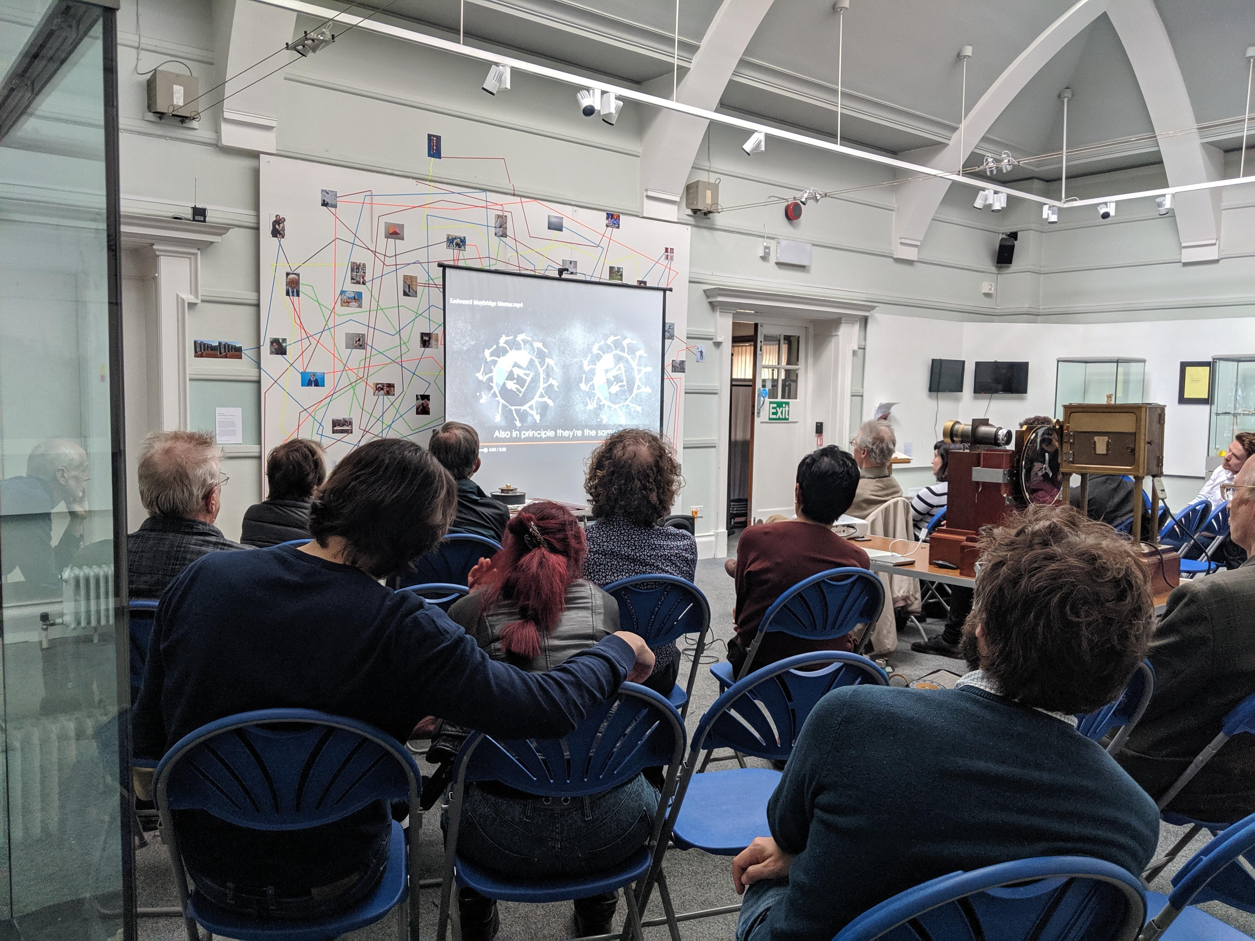 A group of people sat listening to a talk in Kingston Museum