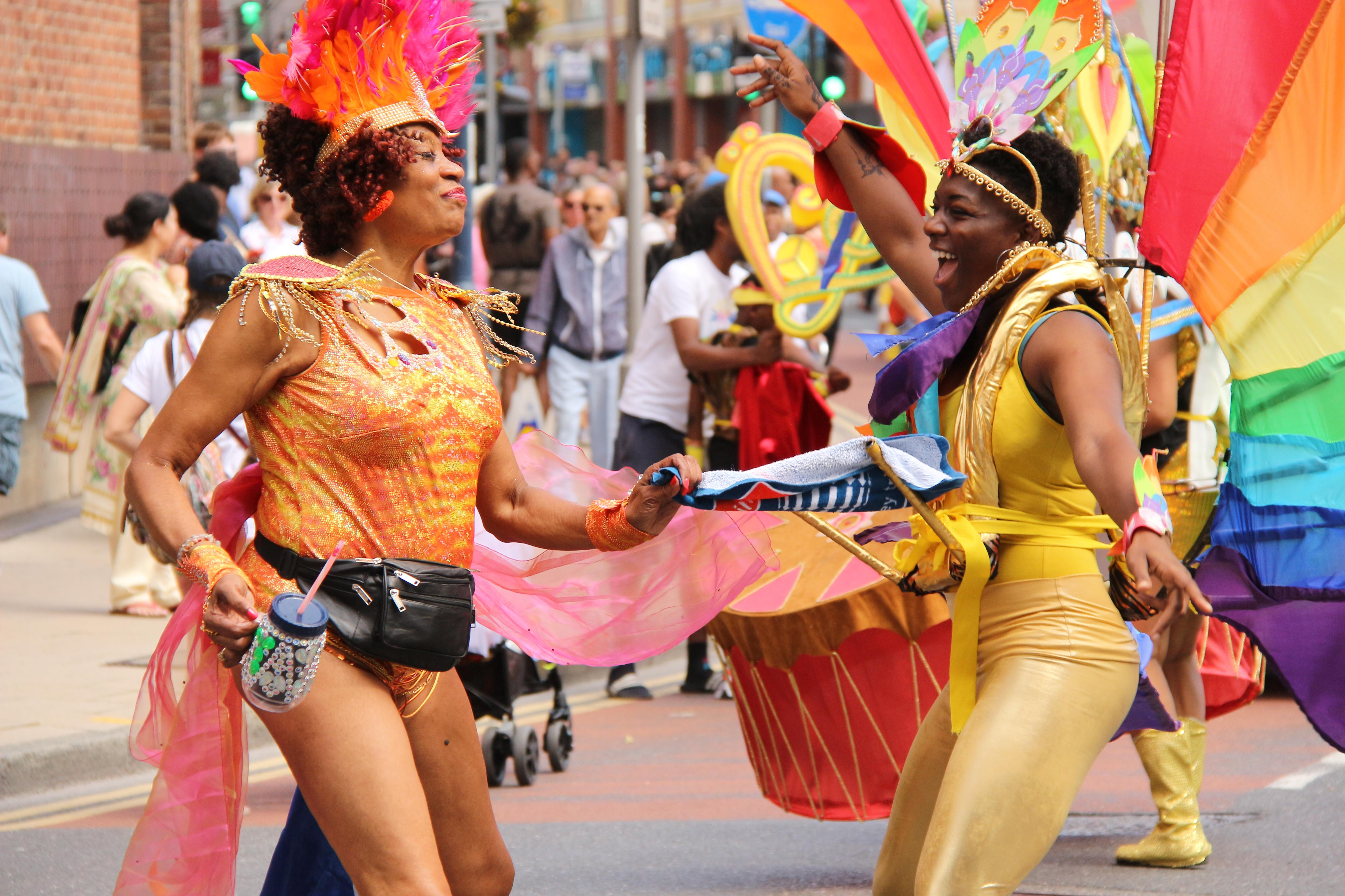 2 women wearing colourful costumes, dancing at Kingston Carnival 2019.